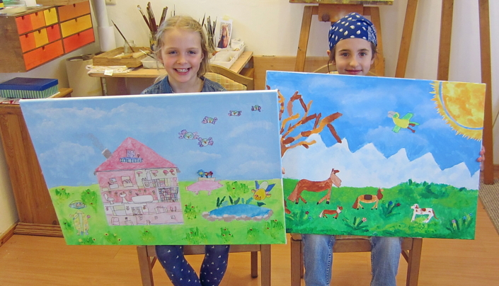 zwei junge Mädchen präsentieren stolz ihre Werke